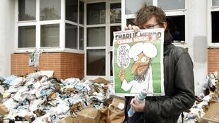 "French cartoonist Luz holds the French satirical magazine Charlie Hebdo renamed ""Charia Hebdo"" as he stands outside the damaged magazine's offices in Paris on 2 November 2011"