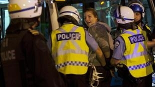 Police detain a protester during a demonstration against a rise in tuition fees