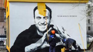 Un trabajador recubre con pintura el grafiti del opositor ruso Alexéi Navalni, en San Petersburgo, Rusia, el 28 de abril de 2021