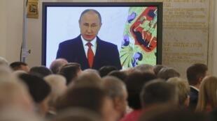 Le président russe Vladimir Poutine sur un écran de télé, durant son discours annuel sur l'état de la nation depuis le Kremlin à Moscou, le 1er décembre 2016.