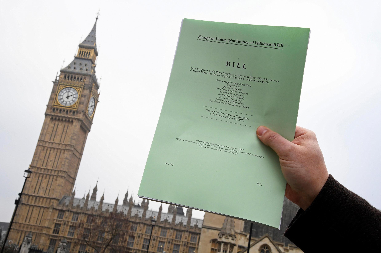 Em frente ao Parlamento britânico, jornalista exibe uma cópia do Artigo 50 do Tratado de Roma, que aciona a saída do Reino Unido da União Europeia.