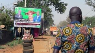Un homme marche près de l'affiche de la campagne électorale de la Guinée pour le parti de la démocratie et de l'harmonie (GDE) à Conakry, Guinée, 26 février 2020.