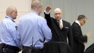 Андерс Брейвик поднимает руку в нацистском приветствии при входе в зал суда 8 июня 2017 г.