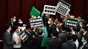 Hong Kong pro-democracy lawmakers holding up placards are blocked by security as they protest China's planned national security legislation during a House Committee meeting