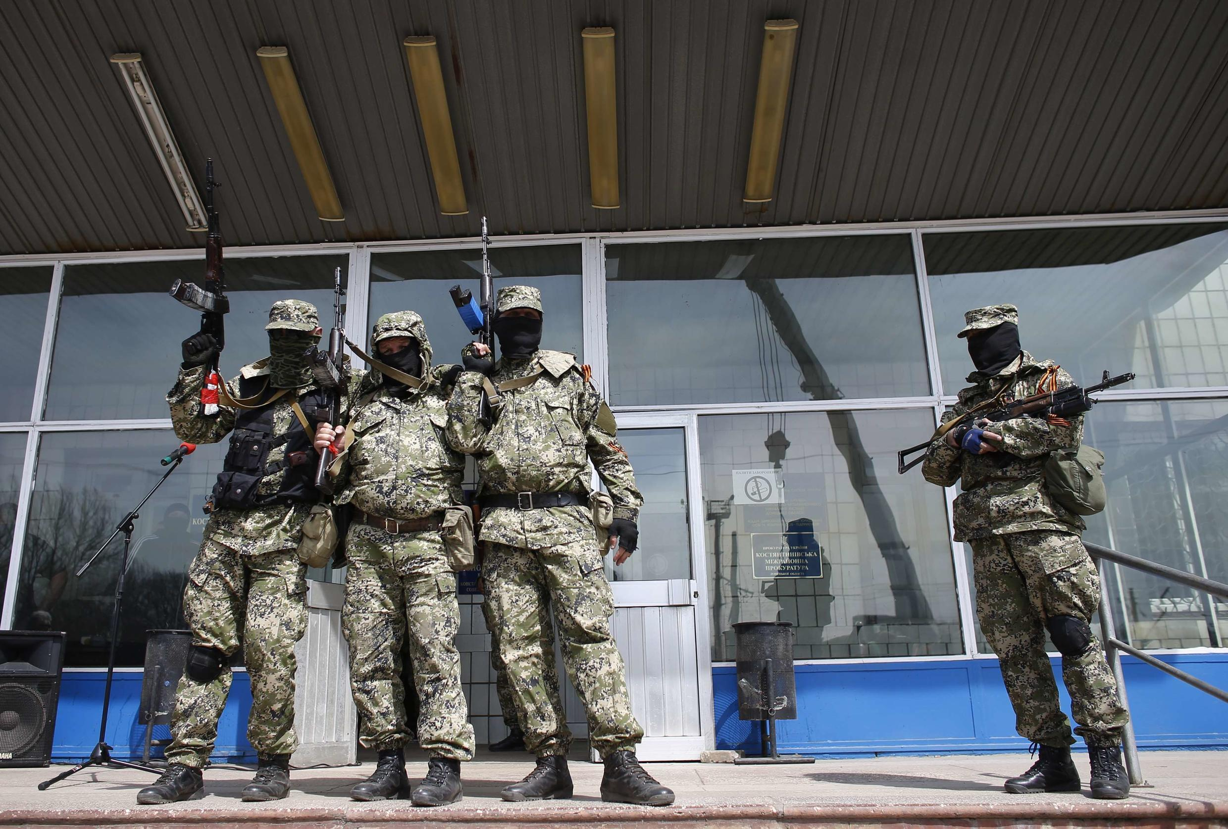Pro-Russian armed men hold their weapons in front of the seized town administration building in Kostyantynivka, 28 April 2014.