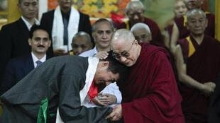 សម្តេចសង្ឃ Dalai Lama (ស្តាំ) ឱបលោក Lobsang Sangay  នាយករដ្ឋមន្ត្រីថ្មីនៃរដ្ឋាភិបាលទីបេនិរទេសបន្ទាប់ពីពិធីសច្ចាប្រណិធានហើយនៅវិហារ Tsuglakhang នៅ Dharamsala ថ្ងៃទី៨សីហា២០១១។