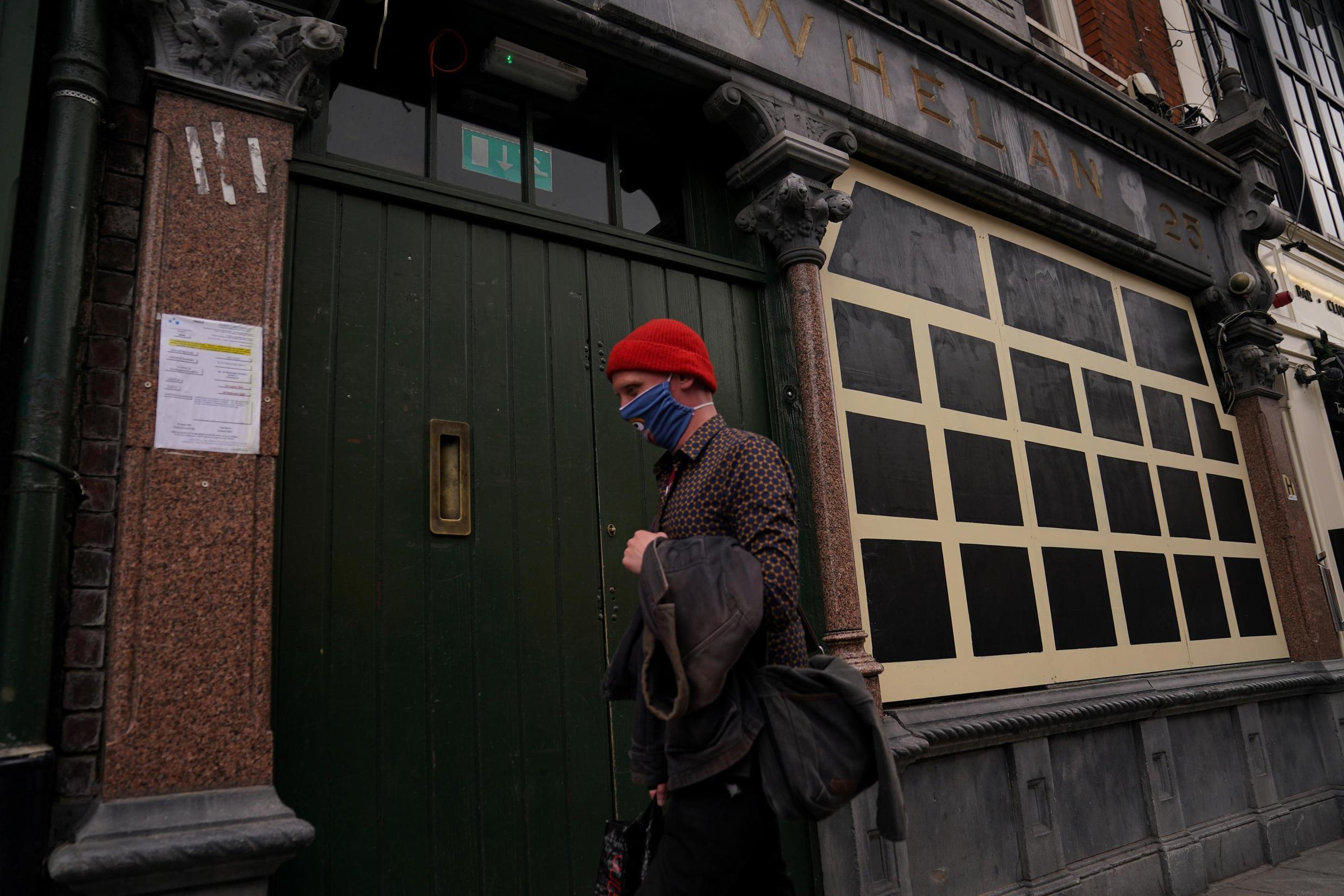 A person wearing a mask walks past a closed pub in downtown Dublin, 3 September 2020.