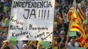 Manifestation en catalogne. On peut lire sur la banderole: «L'indépendance maintenant. Voleurs, politiciens et banquiers, allez en Espagne!»