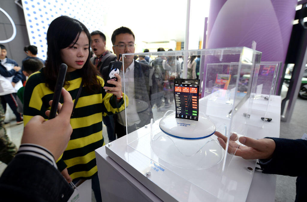 Des visiteurs prennent des photos d'un téléphone mobile à écran flexible lors d'un salon de l'innovation à Chengdu, le 9 octobre 2018.