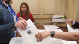 Une électrice de la diaspora libanaise dépose son bulletin dans l'urne au consulat du Liban à Paris, le 29 avril 2018.