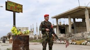 """Un soldat de l'armée syrienne monte la garde à côté d'un panneau indiquant """"Saraqeb"""", dans la ville de Tall Sultan, dans la province d'Idleb."""