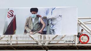 An overpass in Tehran bears a banner showing Iran's supreme leader Ayatollah Ali Khamenei receiving a Covid vaccine