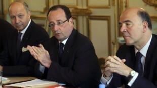 François Hollande (C) entouré du ministre des Affaires étrangères,  Laurent Fabius (G) et du ministre des Finances, Pierre Moscovici lors d'une réunion de travail à l'Elysée, le 24 avril 2013.