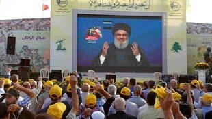 Hezbollah chief Hassan Nasrallah addresses supporters via a screen. He warned that the group would retaliate against Israel for Sunday's attack.