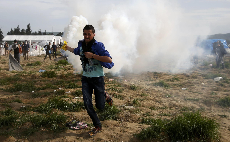 Un migrante camina entre la nube de gases lacrimógenos en Idomeni, en la frontera entre Grecia y Macedonia, el 10 de abril de 2016.