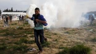 یک پناهجو هنگام فرار از منطقه ای که روز 10 آوریل 2010 هدف گاز اشک آور پلیس مقدونیه قرار گرفت.