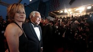 Dominique Strauss-Kahn (C) and Myriam L'Aouffir (L) pose for photographers on the red carpet at Cannes