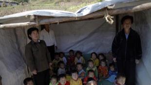 Trẻ em ở một nhà trẻ Bắc Triều Tiên sống tạm trong lều vì trường đã bị lũ lụt phá hủy, đang chờ đợi khám độ suy dinh dưỡng ngày 30/09/2011.
