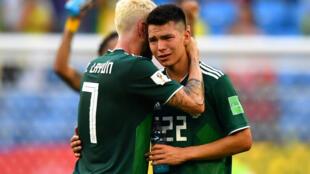 Los mexicanos Hirving Lozano y Miguel Layun se consuelan tras la derrota de Mexico por 2-0 ante Brasil en los octavos de final del Mundial de Rusia 2018.