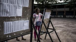 Une observatrice inspecte la liste électorale d'un bureau de vote de Kinshasa le 29 décembre 2018.