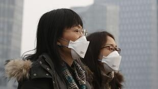 Des jeunes portant des masques filtrants pour se protéger de la pollution à Shanghai. (Photo d'illustration)