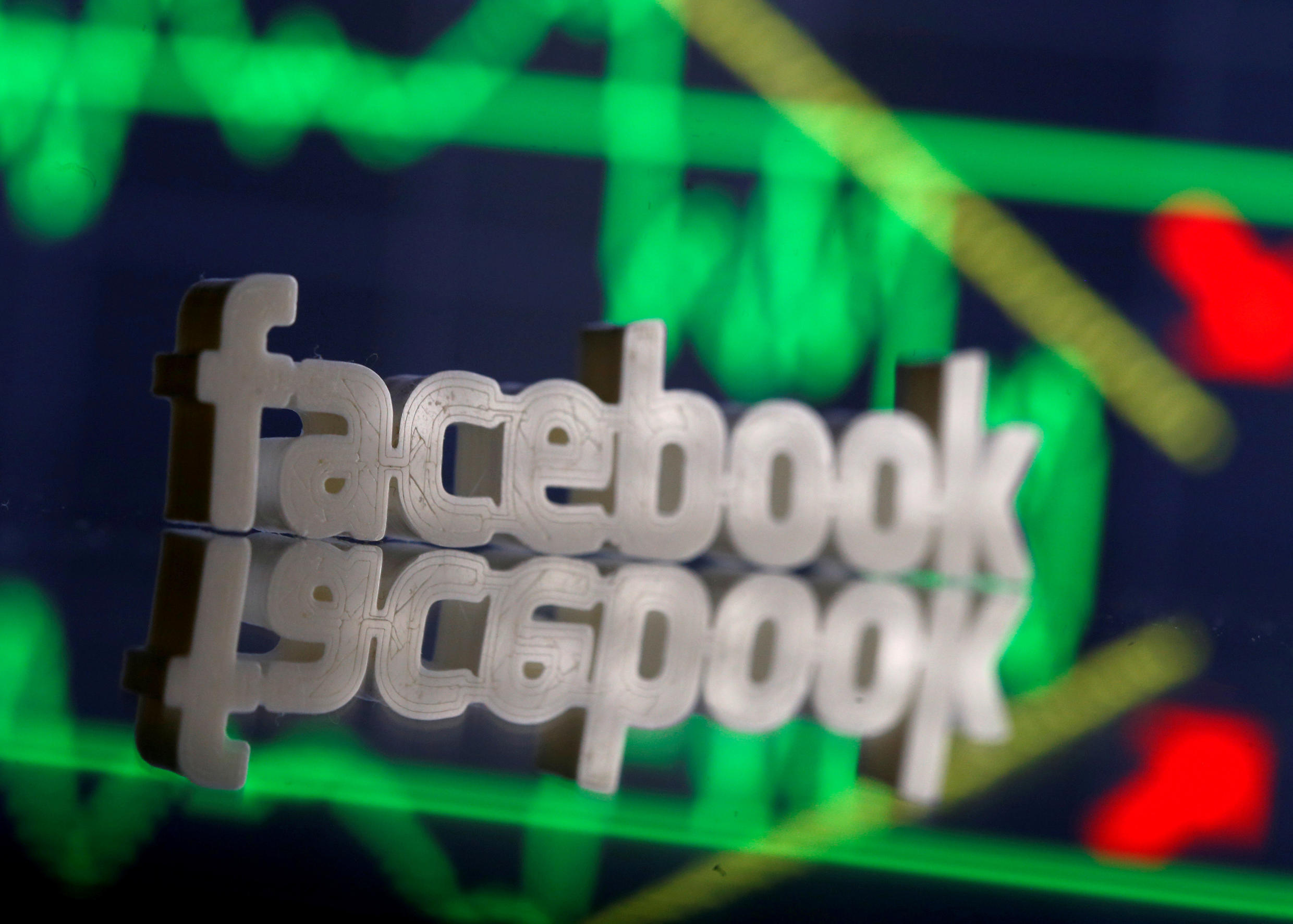 A 3D-printed Facebook logo is seen in front of displayed stock graph in this illustration photo, March 20, 2018.