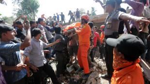 Des secouristes et des policiers transportent une victime du séisme, à Lueng Putu, dans la province d'Aceh, le 7 décembre 2016.