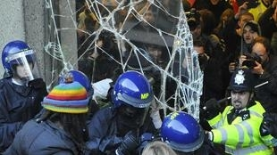 Police and demonstrators confront each other outside Tory HQ