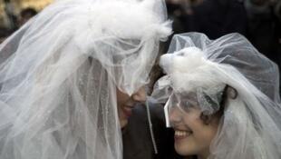 Des militants du mariage pour tous miment un mariage entre femmes, devant le parvis de Notre-Dame de Paris, le 16 décembre 2012.