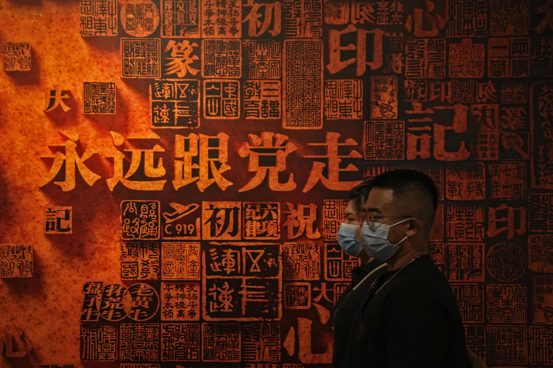 北京,一对男女走过中共1921-2021成就的一堵宣传墙