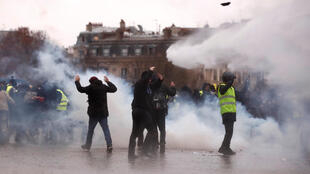 """Protesters walk through tear gas during a demonstration of the """"yellow vests"""" movement near the Arc de Triomphe in Paris, France, January 12, 2019."""