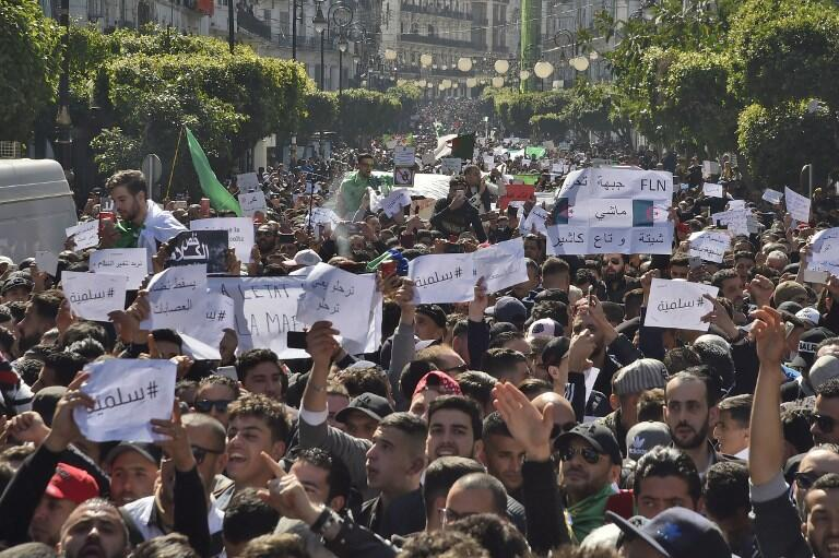 """Algerians march with protest sings reading """"peaceful"""", and """"leave means leave"""" in Arabic, during a rally against ailing President Abdelaziz Bouteflika's bid for a fifth term in power, in the capital Algiers on March 1, 2019."""