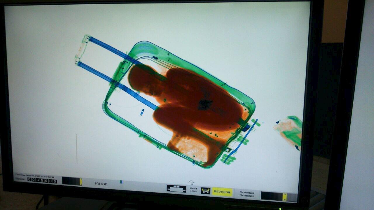 Menino de oito anos é visto dentro de uma mala através de um aparelho de scanner da polícia espanhola.