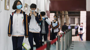 High school students enter a school in Wuhan, capital city of China's Hubei Province, where the coronavirus outbreak was first reported in December 2019.
