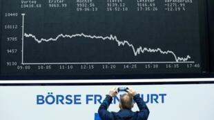Un homme prend en photo le cours de la Bourse de Francfort qui s'effondre le 12 mars 2020.