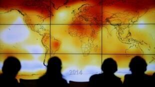 Silhouettes de participants à la COP21 au Bourget, près de Paris, le 8 décembre 2015, devant une carte des changements climatiques à l'échelle de la planète.