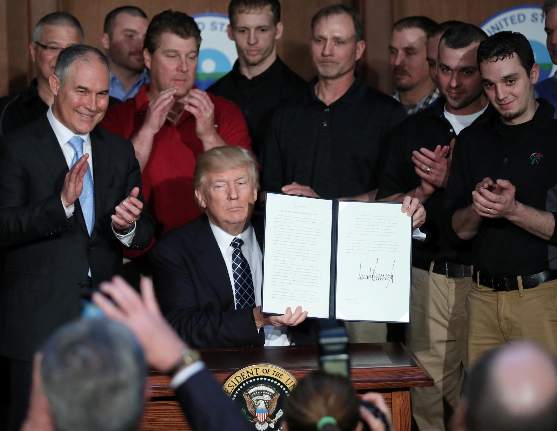 "US President Donald Trump holds up an executive order on ""energy independence,"" eliminating Obama-era climate change regulations"