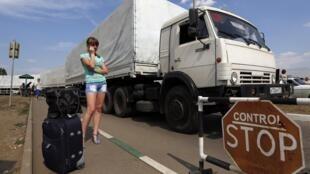 Ngày 22/08, đoàn xe Nga vượt biên giới trước khi được Kiev cho phép. Trong ảnh, xe Nga tại cửa khẩu Donetsk, một phụ nữ đợi con trai chạy nạn từ miền đông Ukraina sang Nga.
