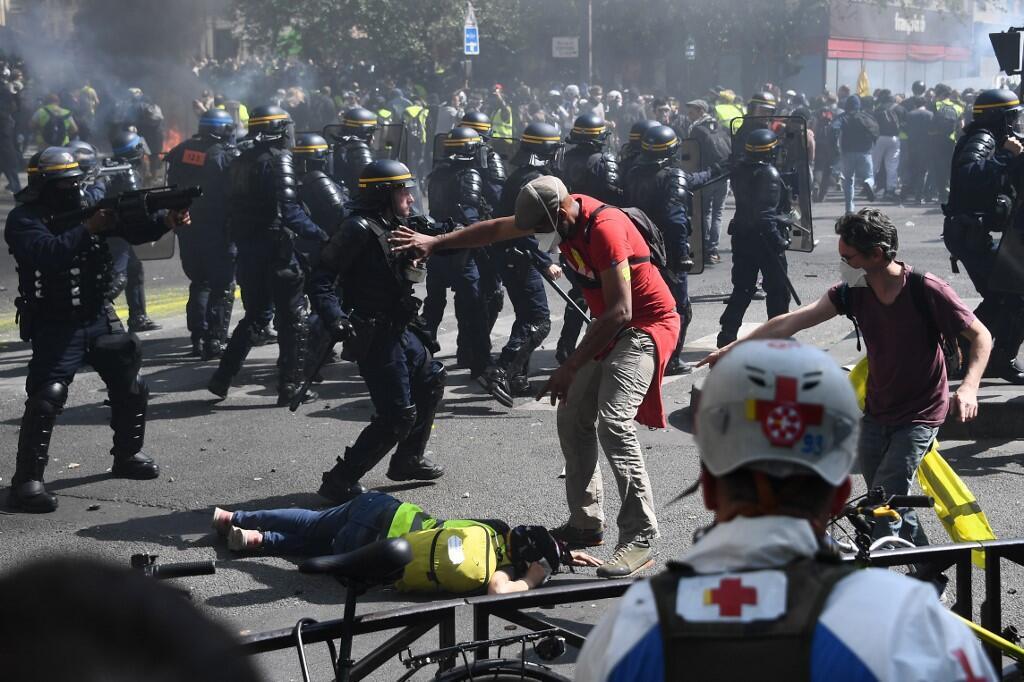 """Manifestante tenta afastar policial de um """"colete amarelo"""" caído no chão, na Praça da República. 20/04/ 2019"""