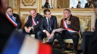 امانوئل ماکرون، رئیس جمهوری فرانسه، (نفر وسط) در کنار «وانیک بربریان»، رئیس انجمن شهرداران شهرکهای روستائی (نفر سمت راست) و «میشل فورنیه»، دبیر کل این انجمن (نفر سمت چپ)