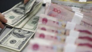 Nhân viên một chi nhánh Ngân hàng Nông nghiệp Trung Quốc đếm những tờ tiền mệnh giá 100 đô la và 100 NDT, tại thành phố Quỳnh Hải, ngày 12/11/2012.