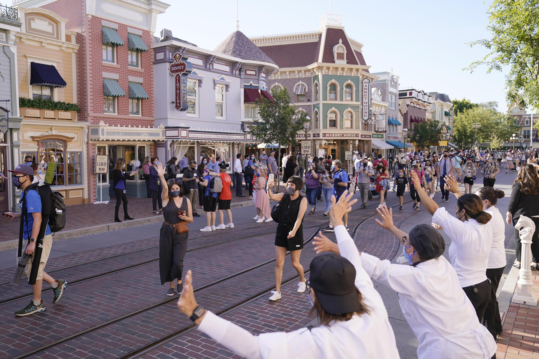 Los visitantes  caminan por Main Street USA en Disneylandia en Anaheim, California, el viernes 30 de abril de 2021. El icónico parque temático del sur de California que estaba cerrado bajo las estrictas normas estatales sobre el virus abrió sus puertas el viernes y algunos visitantes entraron animados y gritando de felicidad