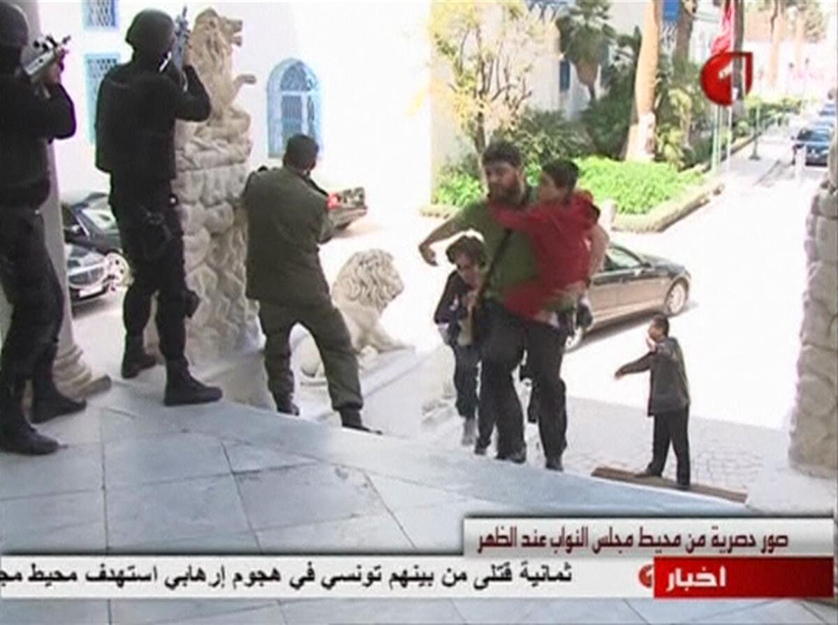 Cette image extraite d'une vidéo de la télévision tunisienne montre un touriste courant se mettre à l'abri tandis que des forces de l'ordre cernent le musée, le 18 mars 2015.