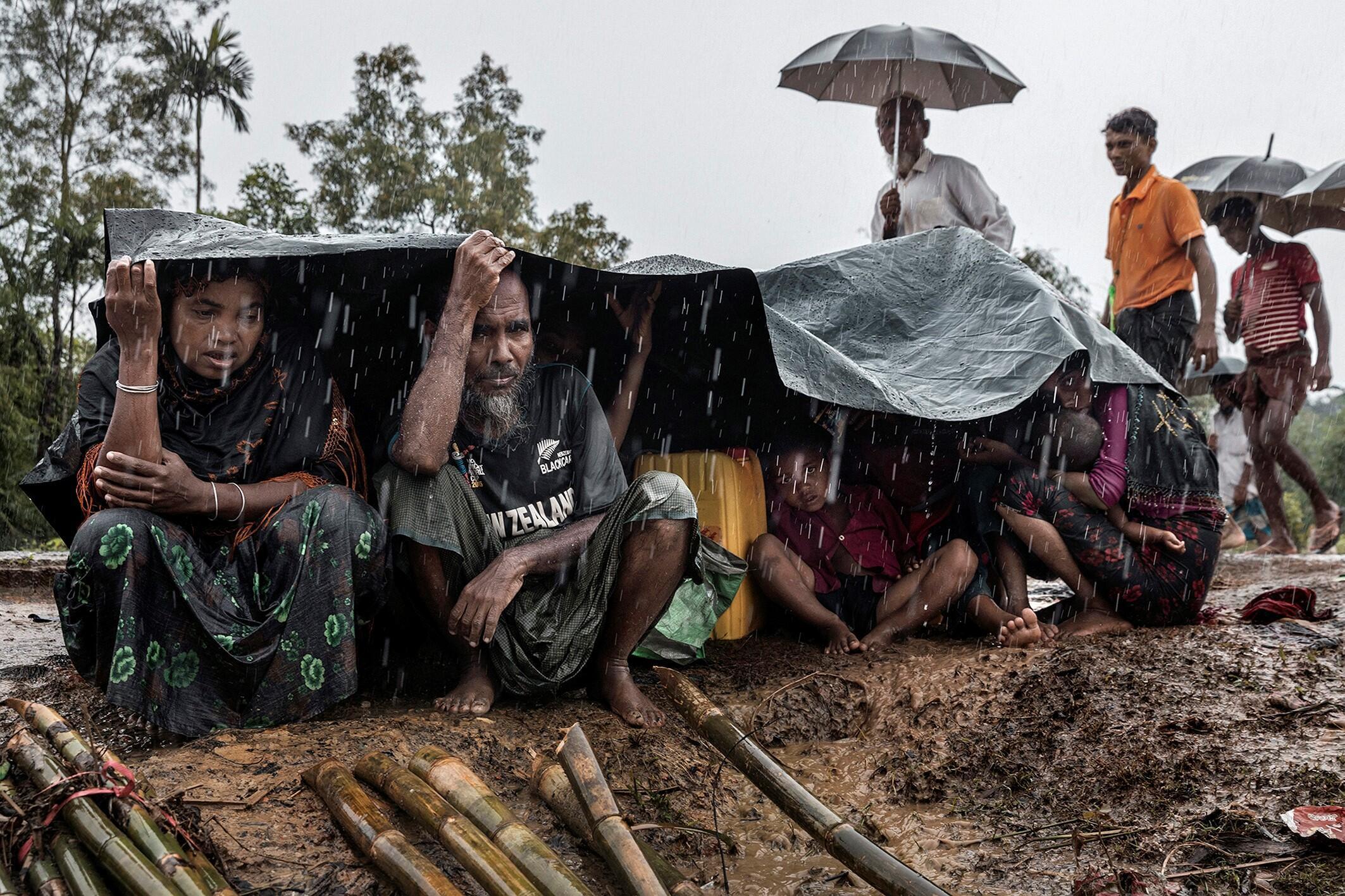 Kutupalong, Bangladesh, 17 de septiembre de 2017. Una familia rohinyá espera un refugio bajo una lluvia torrencial.