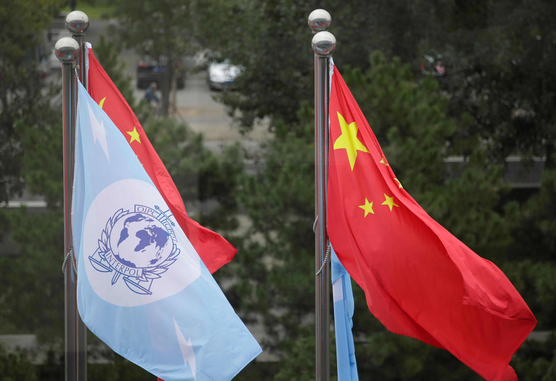 图为国际刑警组织旗帜与中国国旗于北京大会
