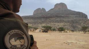 Un soldat français de l'opération Barkhane Force debout sur une base FAMa (Forces armées maliennes) avec le mont Hombori en arrière-plan.