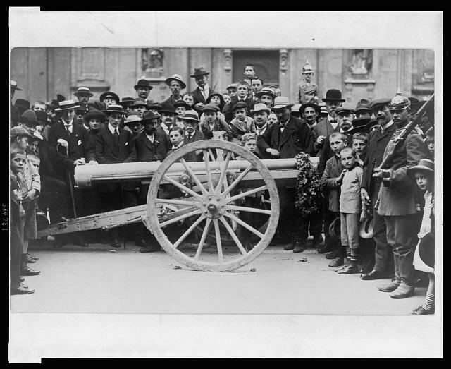 Crowd of German civilians, including children, surrounding a cannon which has a garland hanging from the muzzle