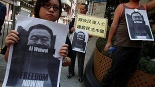 Protesters in Hong Kong carry pictures of detained Chinese artist Ai Weiwei.