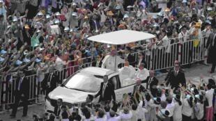 Papa Francisco acena para fiéis ao chegar para celebrar uma missa ao ar livre em Seul neste sábado (16).