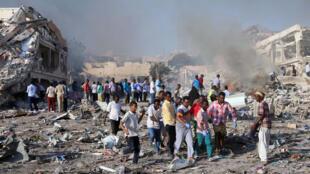Des civils retirent le corps de victimes de l'attentat à la voiture piégée perpétré devant un hôtel à un carrefour commercial fréquenté du centre de Mogadiscio, le 14 octobre 2017.
